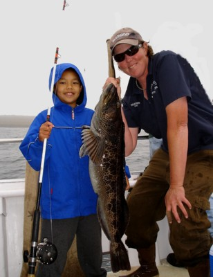 Raymond Li gives Heather a hand to show off the 21 pound whopper lingcod he caught on July 26